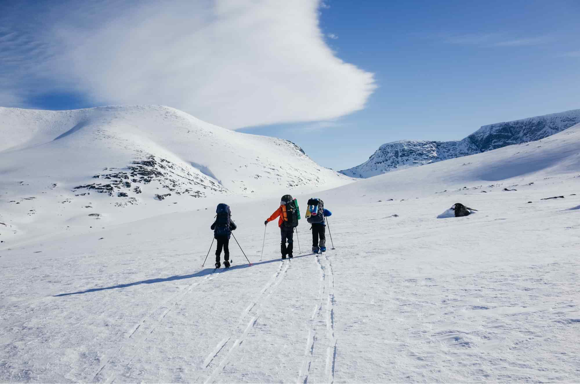 Group of 3 cross country skiers on mountain