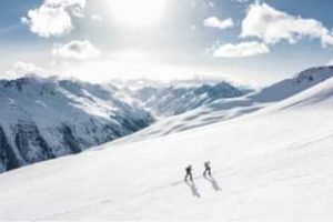 Two people cross-country skiing in the mountains