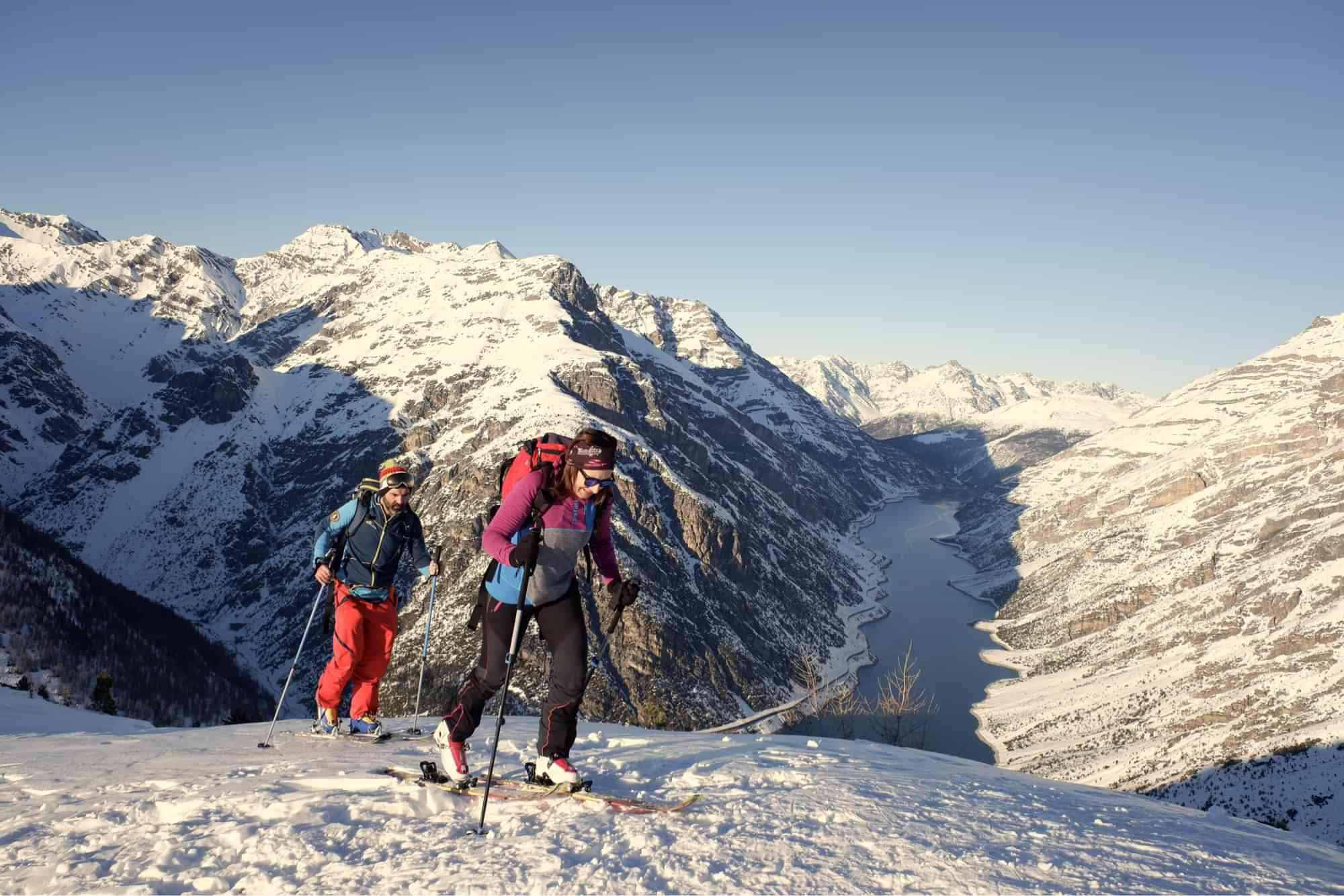 Woman and man during skimo competition to mountain summit